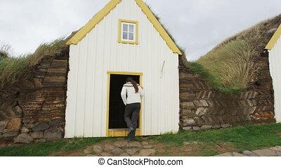 Iceland tourist by Old Farmhouse Laufas Glaumbaer farm Folk Museum turf roof houses in Varmahlid, Skagafjordur. Icelandic tourist destination and attraction landmark. Woman walking Icelandic sweater.