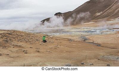 Iceland volcano mudpot hot spring landmark destination: Namafjall Hverarondor hverir mudpot also called mud pool hot spring or fumarole. Beautiful Icelandic nature. Man photographer. RED EPIC SLOW.