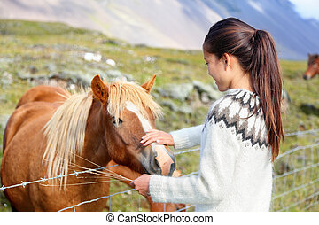 Icelandic horses - woman petting horse on Iceland