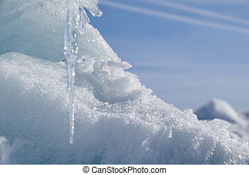 Icicle, ice and snow on blue sky background.