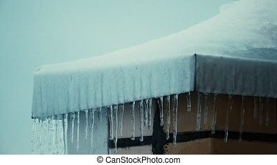 Icicles and snowy sloped roofs of residential houses in...