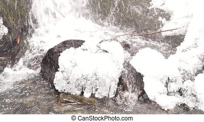 Icicles bellow waterfall. Snowy and icy stones and boulders...