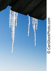 Icicles border on blue sky background