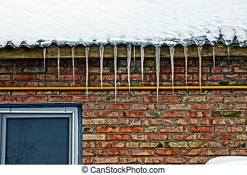 icicles from a roof on a brick wall with a window