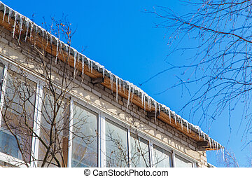 Icicles hanging from the roof. Winter in town.