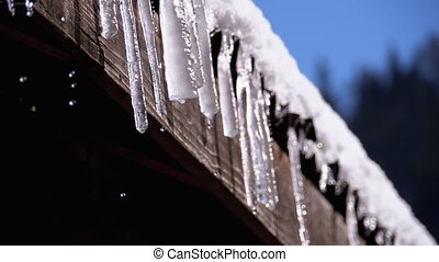 Icicles Melt and Dripping on the Sun Hanging on the Roof of a Wooden House. Slow Motion in 180 fps. Winter Sunny Day. Warming. Spring Sun shining on Dripping Icicles. Water rapidly dripping from their tips. The winter sunlight is shining.