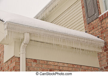 Icicles hanging on the edge of the roof along the frozen gutter in a winter snow storm.