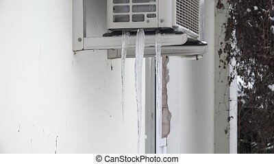 Icicles on the air conditioner hanging on house wall in winter time. 4K