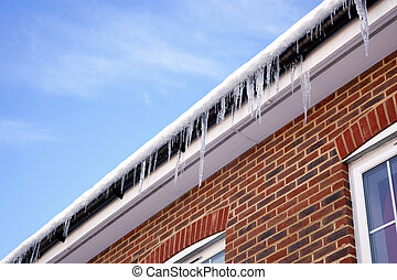 Icicles on the gutter - Winter image of icicles hanging from...