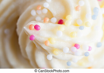 Close up (macro) of a cake topping made from swirled buttercream icing and colourful decorative sprinkles.