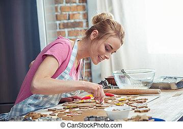 Icing Christmas cookies - Teenage girl wearing apron and...