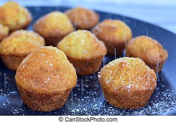 Icing sugar on mini muffins - Sprinkling icing sugar on mini...