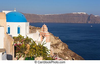 Iconic church with blue cupola and pink bell tower in Oia, Santo