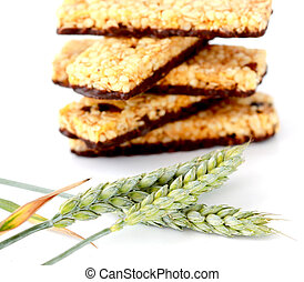 Healthy granola bar and green wheat on white background