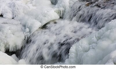 Icy Cascade Loop - Water splashes down a wintry, partially...