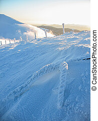 Icy fence posts on the hillside. Mountain winter landscape in the Carpathians in Ukraine.