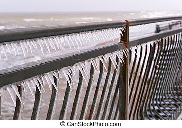 icy iron fence, metal fence covered with icicles