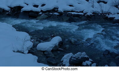 Icy Mountain River At Dusk - River cutting through thick...