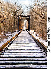 Railroad tracks lead to a trestle and all is covered in a layer of ice after an ice storm