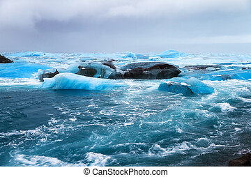Beautiful view of the flowing water in the river leading to the sea from the Jokulsarlon lake with icebergs in winter