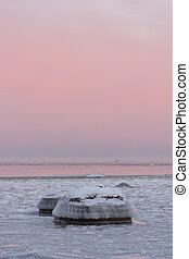 Icy rocks in sea at sunrise or sunset