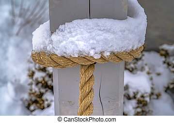 Icy snow on the rope tied to a wooden post
