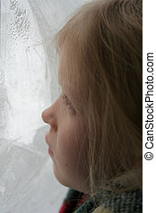 Icy window - A little girl looking through the icy window