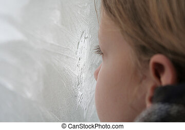 Icy window - A young girl looking through the icy window
