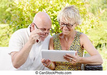 idade média, par, sorrindo, usando, um, tabuleta, em, seu, jardim