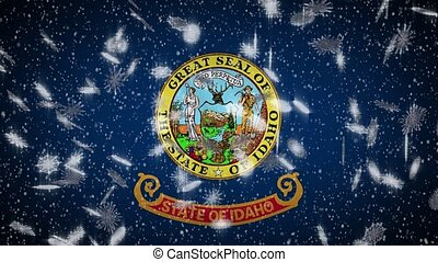 Idaho flag falling snow, New Year and Christmas background, loop.