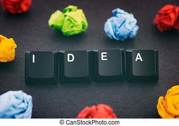 The word Idea on a black background with some colorful crumpled paper balls around it