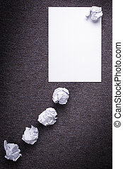 Crumpled paper with a thought balloon concept and crumpled paper attempts leading to it