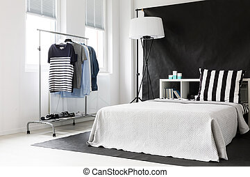Black and white bedroom in ascetic style with window, functional clothes rack and bed