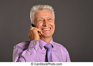 Ideal elderly man with phone in suit on black background