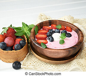 Ideas for healthy summer breakfast op dessert. Smoothies in bowls with strawberry, blueberry berry. With oatmeal, fresh berries.