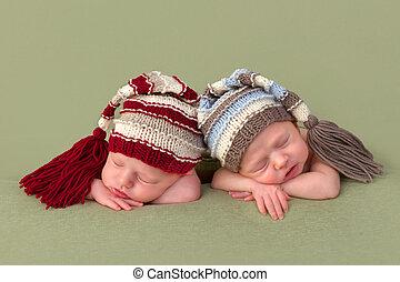3 weeks old identical twin girls sleeping on a green backdrop