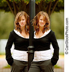 Waiting At The Bus Stop - identical twin women standing at the bus stop and leaning on a pole.