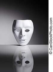 Identity - White blank plastic mask on reflective surface.