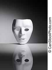 Identity - White blank plastic mask on reflective surface.