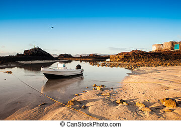 Idilic beack - a boat in the beach at sunset