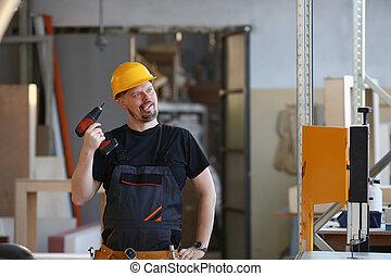 Idiot worker using electric drill portrait. Manual job DIY...