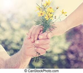 idoso, e, mulher jovem, segurar floresce, exterior