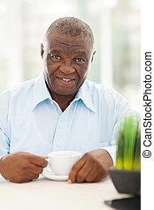 idoso, homem americano africano, comendo café