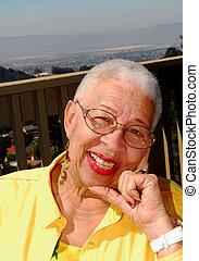 idoso, mulher americana africana, sentando, ao ar livre
