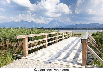 Idyllic Allgaeu - Wooden bridge over a brook near lake...