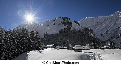 idyllic austrian mountain village at winter with snow and sunny blue sky