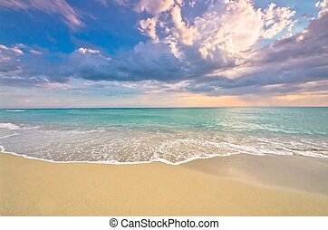 Idyllic empty beach panorama with turquoise ocean, surf and delicate sunset, tropical paradise