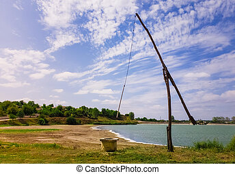 Idyllic countryside scene with an old water well sweep (shadoof) near the Delia lake (Moldova). Also called a counterpoise lift or well pole, is an ancient irrigation tool and used for watering crops.
