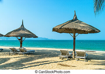 Idyllic landscape paradise scene at the beach side with loungers on clear blue sky day