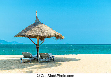 Idyllic landscape paradise scene at the beach with loungers on clear blue sky day